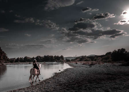 Cowgirl riding pinto horse. River landscape afternoon. Girl, woman, lady in a work uniform and hat is barefoot.