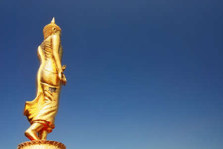Standing Buddha with blue sky photo