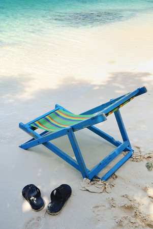 Chair and flipflop sandals on sea beach photo