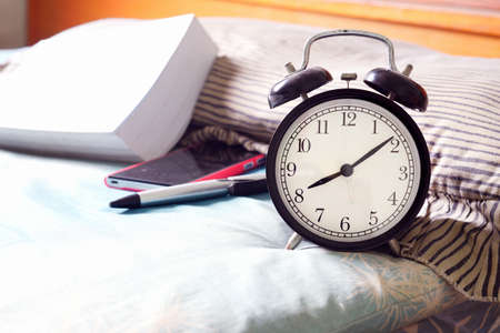 Alarm clock on bed at home  Alarm clock Stock Photo