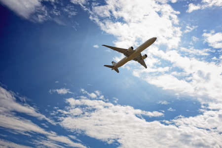Airplane flying against blue sky with clouds   Airplane flying