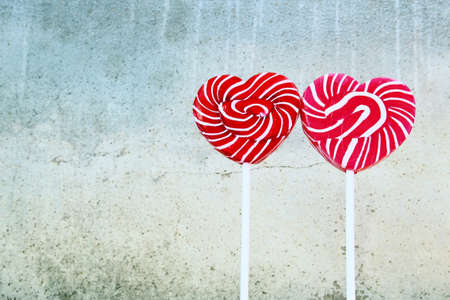 Heartshaped lollipops with old cement background Stock Photo