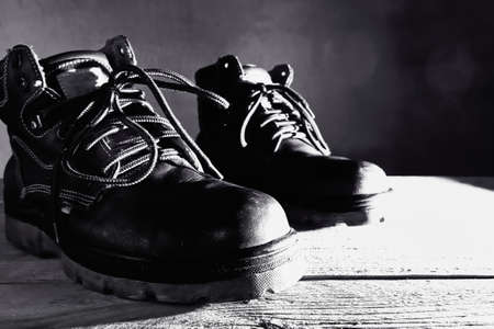 Black and white safety shoes on wooden