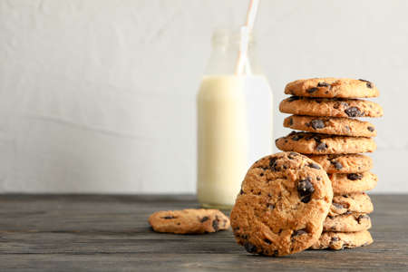 Tasty chocolate chip cookies and bottle of milk on wooden table. Space for text Archivio Fotografico