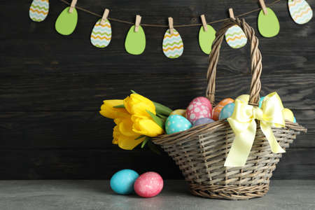 Easter basket filled with colorful eggs and flowers on a wooden background