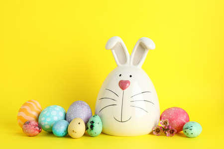 Decorated bunny and Easter eggs on color background. Space for text Stock Photo