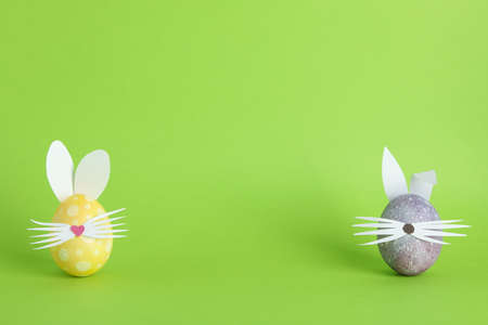Decorated Easter eggs and cute bunnys ears on color background. Space for text