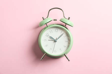 Retro alarm clock on color background, space for text