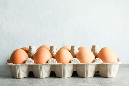 Chicken eggs in carton box on gray background, space for text Stockfoto