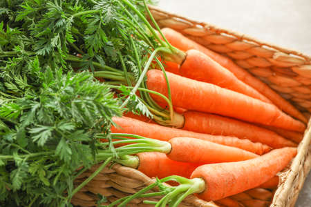 Wicker basket with ripe carrots on grey table, closeup