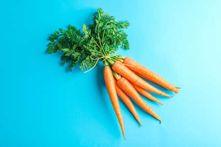 Ripe carrots on blue background, space for text Stok Fotoğraf
