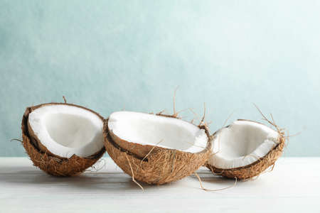 Coconuts on white wooden table against grey background