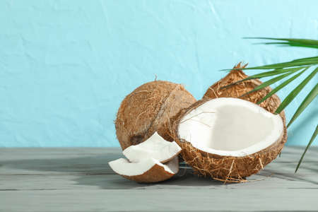Coconuts with palm branch on wooden table against color background