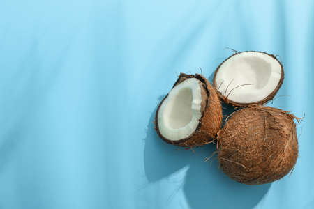Two coconut one of which split on color background