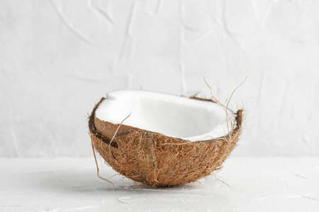 Half tropical coconut on wooden table against white background, space for text