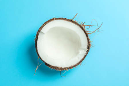 Half tropical coconut on color background, space for text