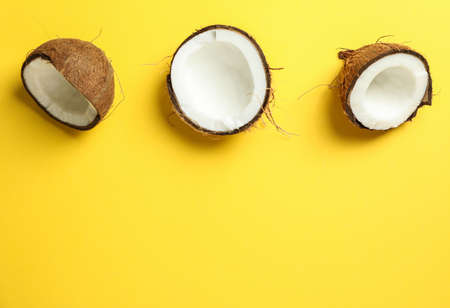 Halves coconut on color background, space for text Stock Photo