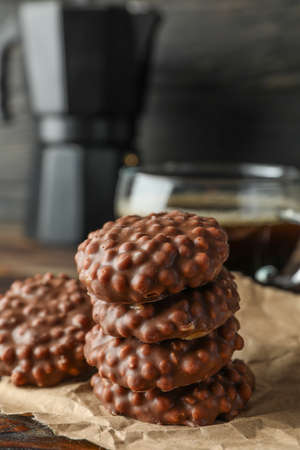 Stack of chocolate cookies and cup of coffee on wooden table against dark background, space for text