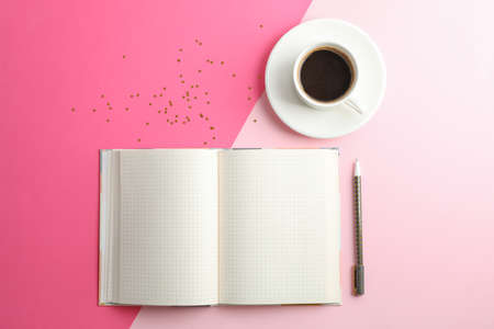Clean copybook with pen and cup of coffee on two tone background