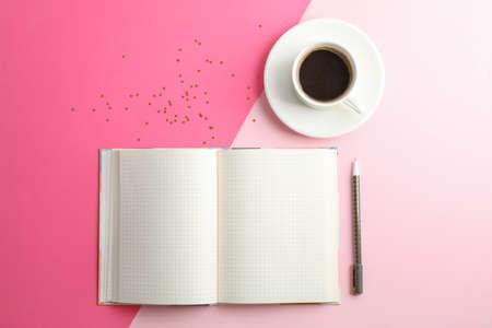 Quaderno pulito con penna e tazza di caffè su sfondo bicolore