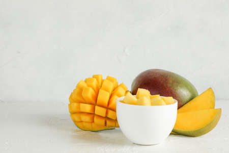 Small bowl with mango pieces and cut mangoes on white background, space for text