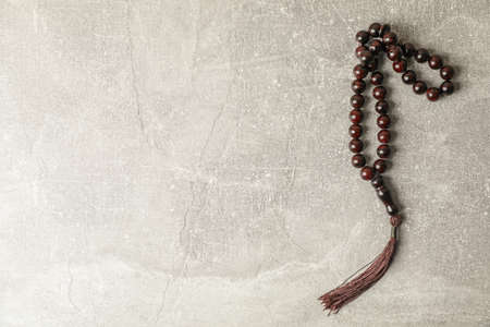 Prayer beads on grey background, space for text