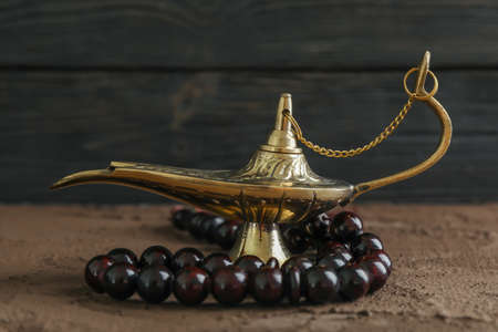 Magical Aladdin Lamp with prayer beads on brown table against wooden background