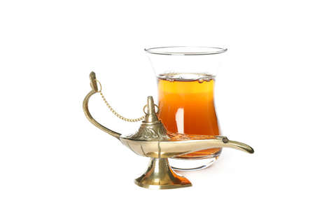 Glass of tea and Aladdin Lamp isolated on white background Stock Photo