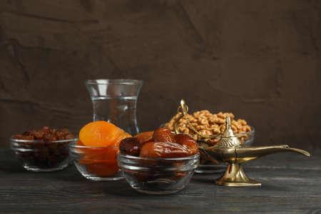 在棕色背景的木制桌子上放着斋月卡里姆的食物和装饰