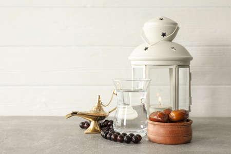 Dekoration und Essen des Ramadan Kareem-Urlaubs auf grauem Tisch vor Holzhintergrund Standard-Bild