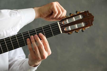 Man tunes classic guitar against dark background, space for text Reklamní fotografie