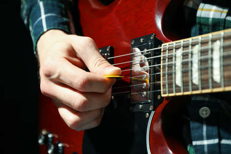 Man playing on electric guitar against dark background, closeup