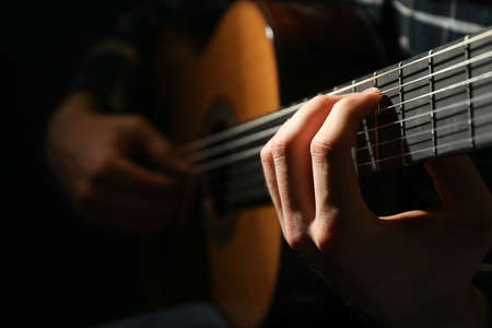 Man playing on classic guitar against dark background, closeup