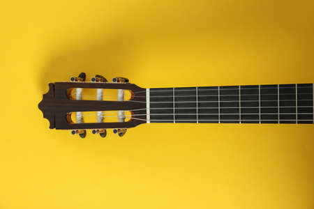 Guitar neck on yellow background, space for text