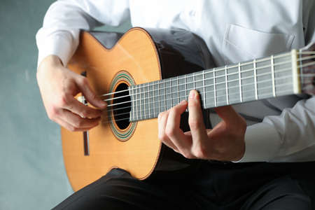 Man playing on classic guitar against light background, space for text Reklamní fotografie