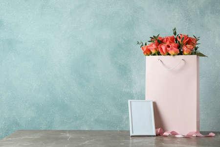 Bolsa de regalo con ramo de rosas rosadas y marco vacío en la mesa gris contra un fondo claro
