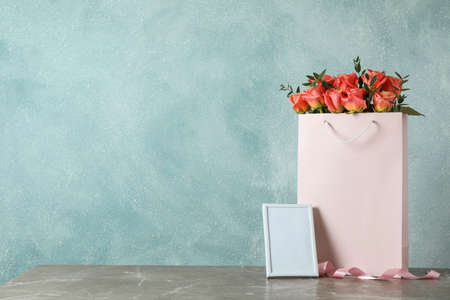 Gift bag with bouquet of pink roses and empty frame on grey table against light background
