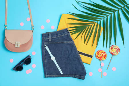 Flat lay composition with: women clothes and accessories, palm leaf and candy canes on blue background. Summer backdrop