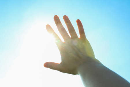 Beautiful blue sky and sun background with woman hand. Wonderful skies Banco de Imagens