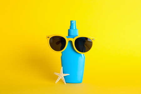 Sunscreen spray with starfish and sunglasses on color background, space for text