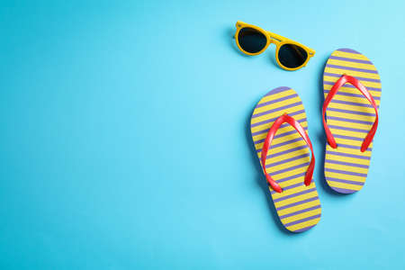 Sunglasses and flip flops on color background, space for text Stockfoto