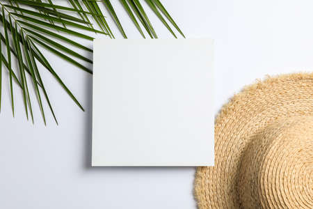 Square with space for text, palm leaves and straw hat on white background, top view