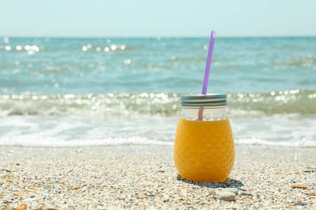 Glass jar of fresh orange juice on seaside, space for text. Summer vacation background Stockfoto