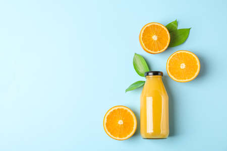 Flat lay composition with fresh orange juice in bottle and oranges with leaves on color background, space for text. Fresh natural drink Stockfoto