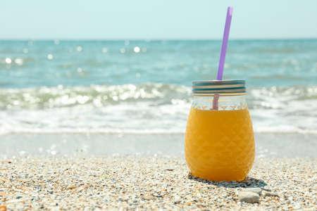 Glass jar of fresh orange juice on seaside, space for text. Summer vacation background Banco de Imagens