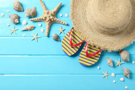 Straw hat, flip flops and many starfishes on color wooden background, space for text and top view. Summer vacation backdrop