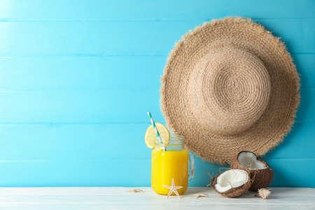 Chapeau de paille, noix de coco, jus d'orange frais et étoiles de mer sur tableau blanc sur fond de bois de couleur, espace pour le texte. Toile de fond de vacances d'été
