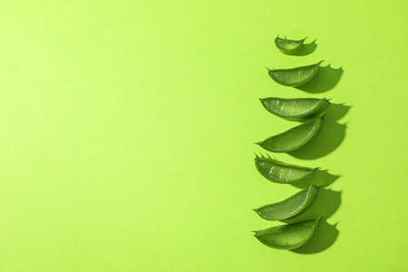 Aloe vera slices on color background, space for text. Natural treatment