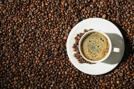 Cup of coffee with frothy foam on beans background, top view and space for text. Coffee time accessories