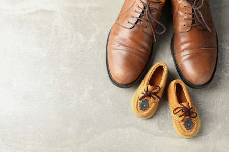 Brown leather shoes and children's shoes on grey background, space for text and top view Фото со стока